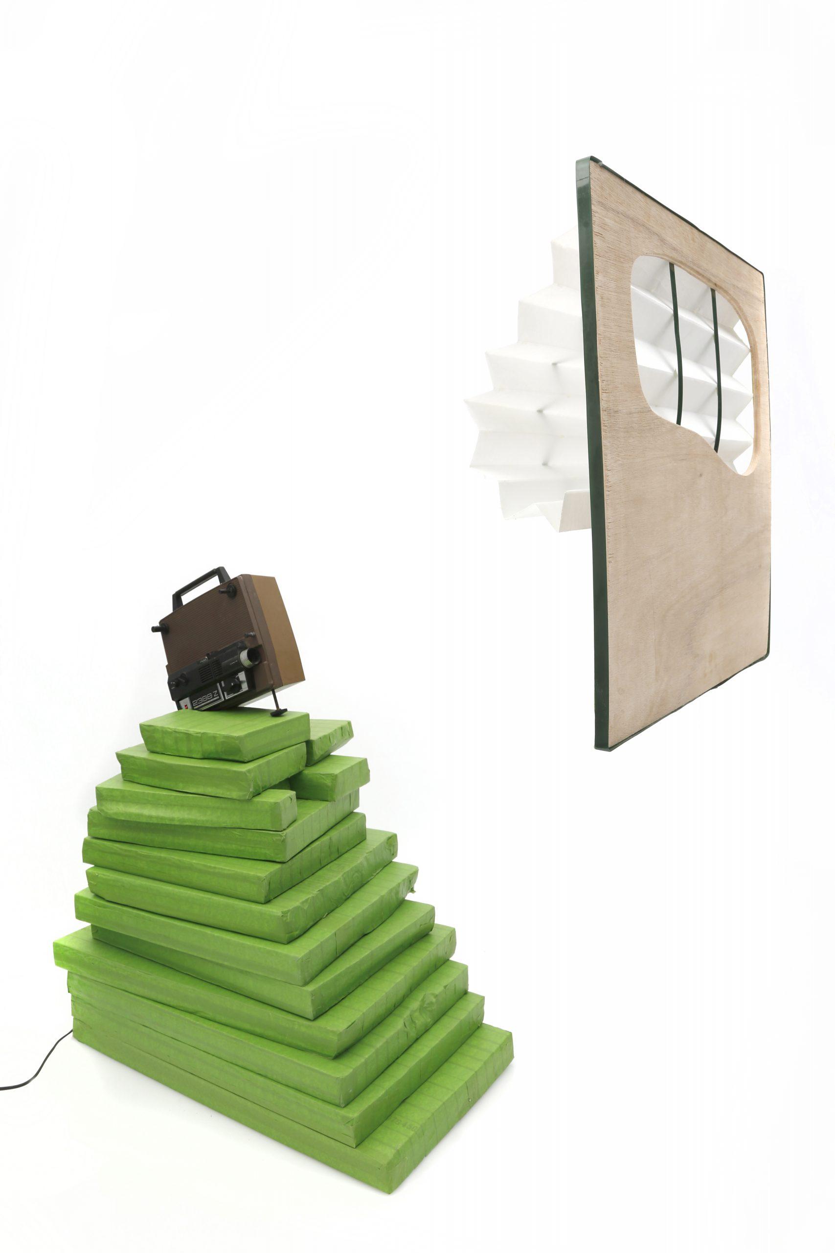 Regina Viqueira, Private Entrance, 2017, frog tape, foam, 8mm projector, wood, air filter, packing belt. Dimensions variable