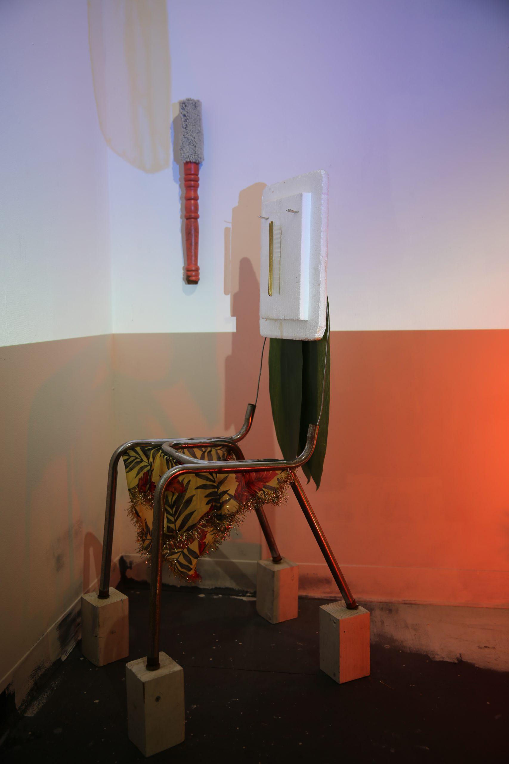 "Lola Queen Supreme (installation view, SVA MFA Open Studios), 2017 chair frame, fabric, tinsel, plastic ti leaves, styrofoam, comb, wire, wood blocks approx. 46"" x 14"" x 21"""