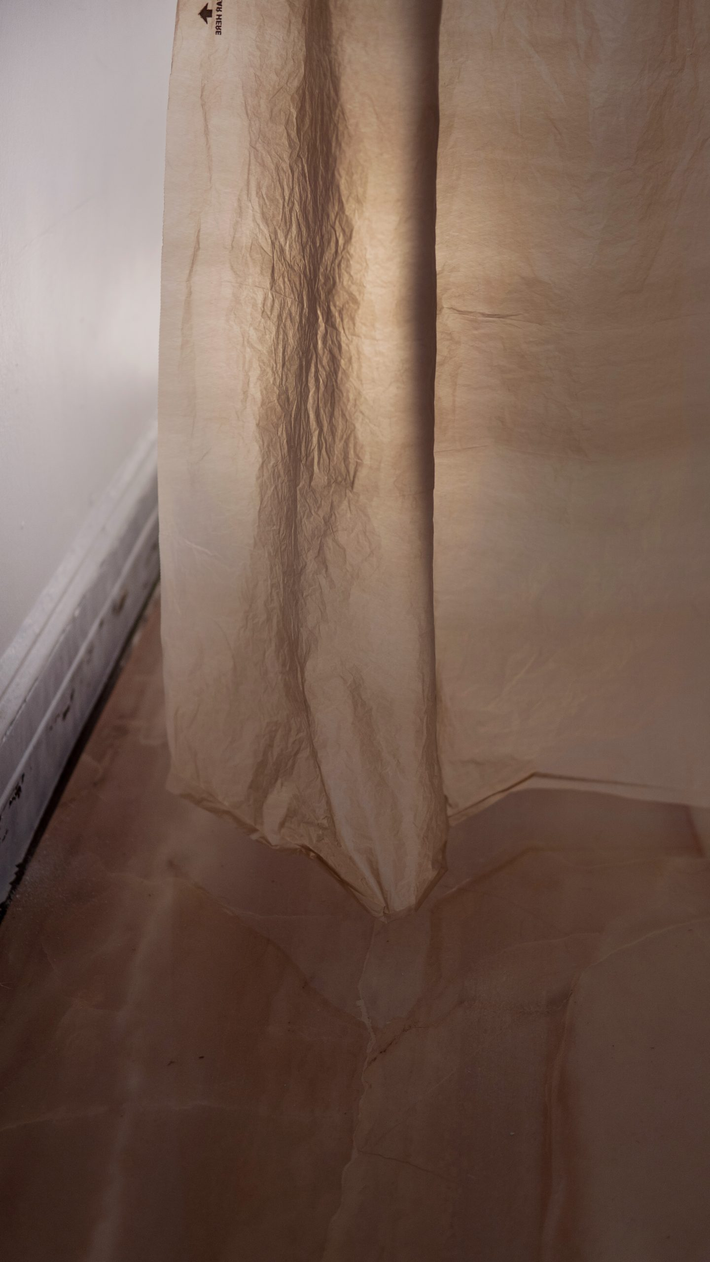 """Regina Viqueira, Installation documentation of """"Luxury Plastic"""", plastic Lowe's bag, shower curtain rings, rope wire, hooks, large format tile, clamp light, dimensions variable"""