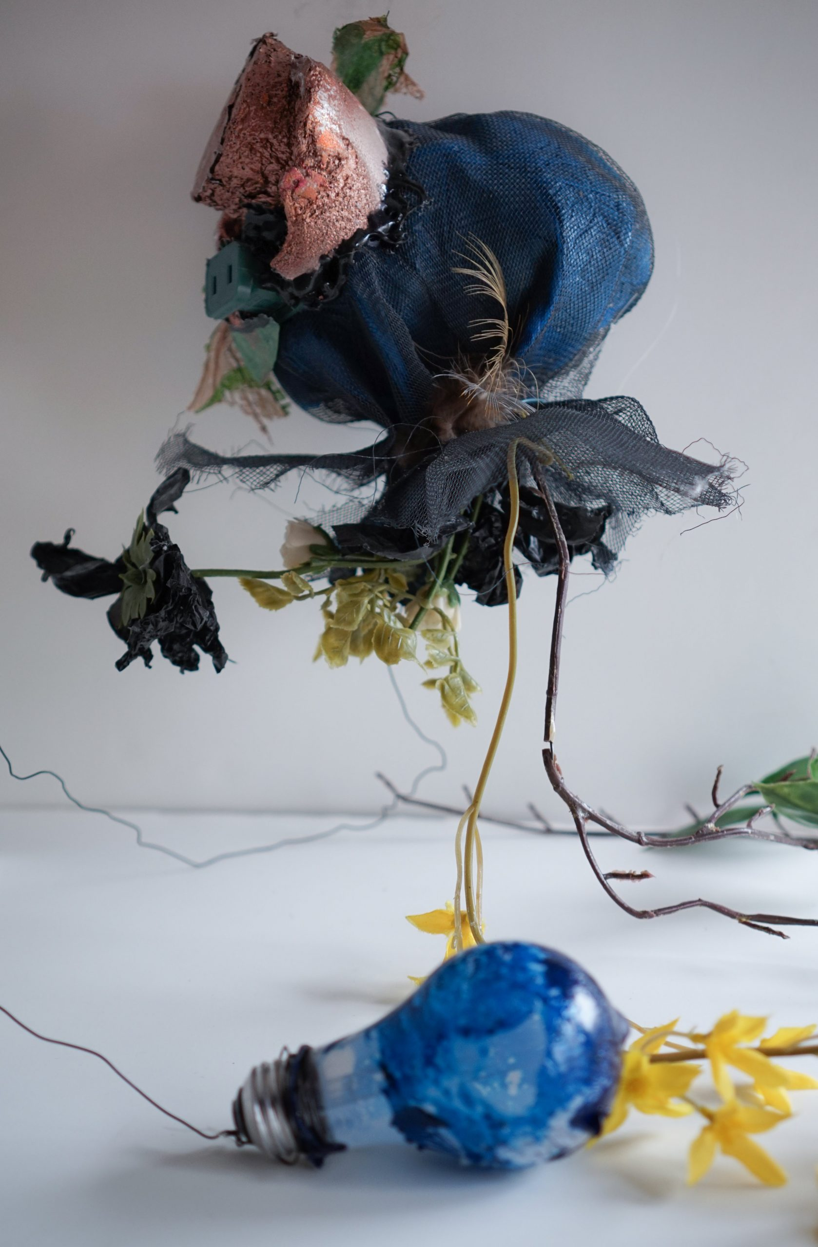 Thingamabob #3. 2014. Mesh, plastic bag, plastic flowers, styrofoam, electrical plug, lightbulb, wire.