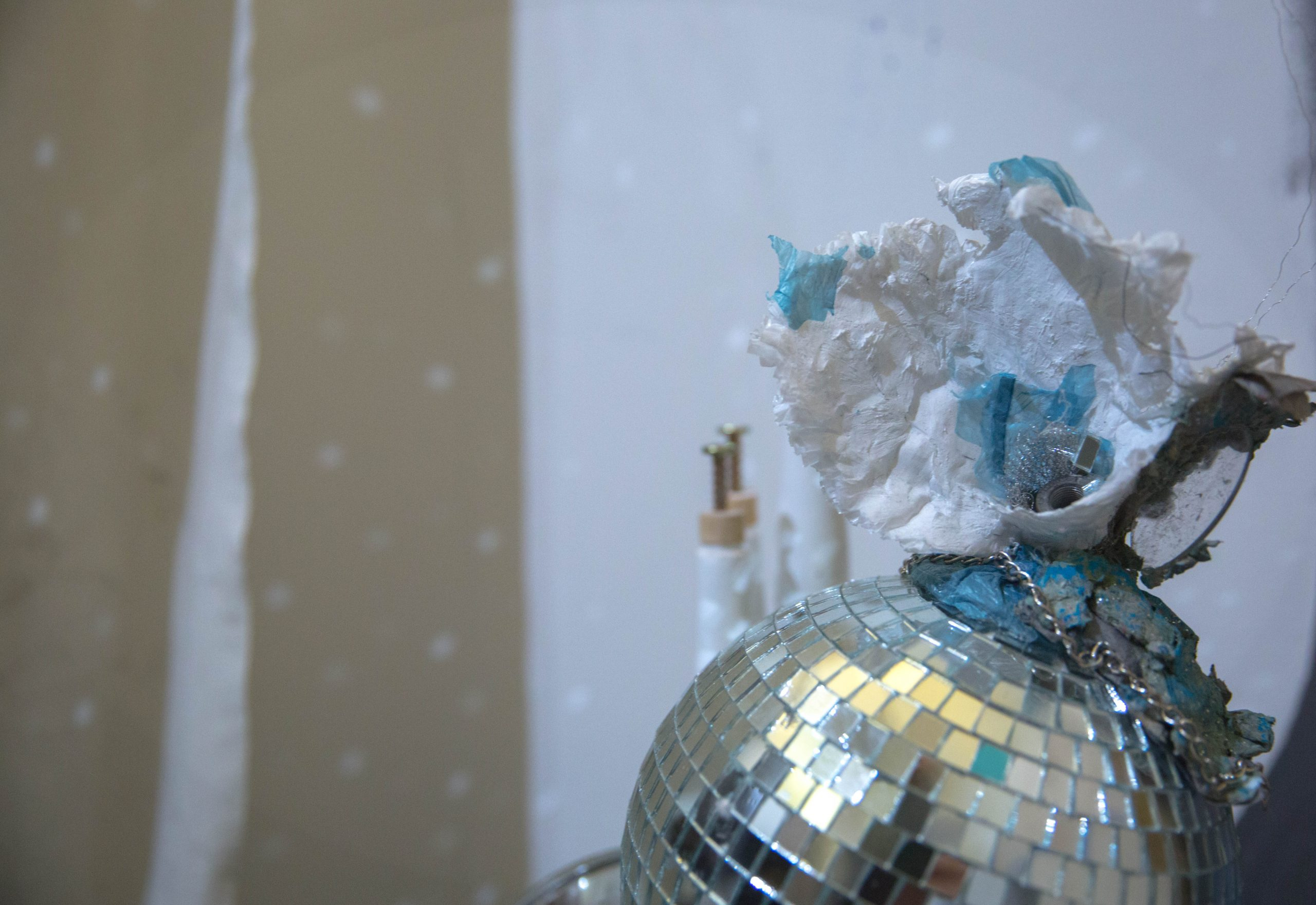 """Globus Purgamentum, 2016, Disco ball, paper pulp, lens from glasses, chain, plastic bags, wire, approx. 12"""" in height and 22.5"""" in diameter."""
